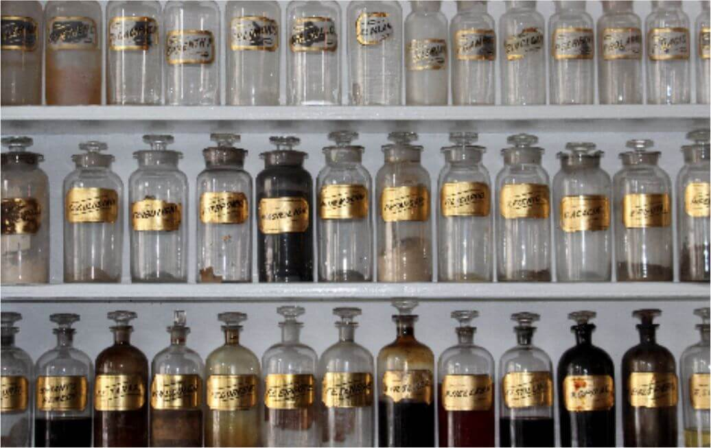 Sun Med Community Wellness Qi Mystical in the Mundane - Glass Bottle with Gold Labels in a Cabinet